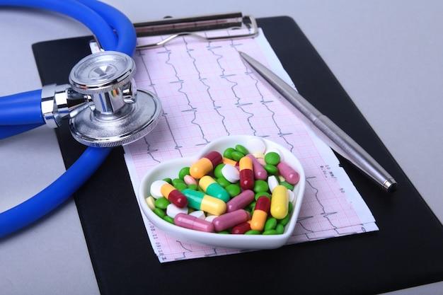 Stethoscoop, rx-recept en kleurrijke assortimentpillen en capsules op plaat. Premium Foto