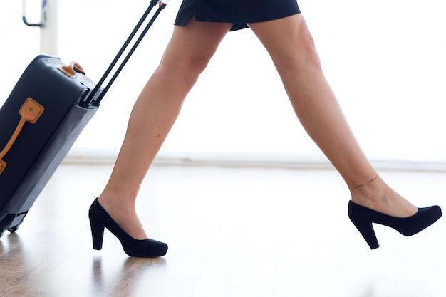 Stewardessbenen met bagage in luchthaven. Premium Foto