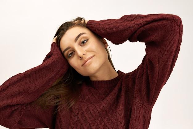Stijl, mode, breigoed en seizoensconcept. portret van aantrekkelijke zelfverzekerde jonge europese vrouw gekleed in warme pullover hand in hand op haar hoofd, camera kijken met een gelukkige vrolijke glimlach Gratis Foto