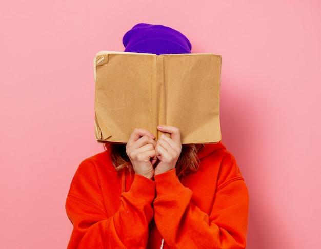 Stijlmeisje in oranje hoodie en purpere hoed met boek op roze muur Premium Foto