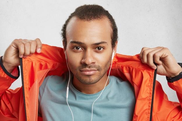 Stijlvol aantrekkelijk mannelijk model met borstelharen, luistert naar muziek maakt gebruik van oortelefoons, houdt de handen op oranje anorak, Gratis Foto