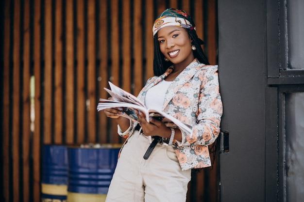 Stijlvol afrikaans amerikaans tijdschrift lezen in de straat Gratis Foto