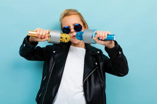 Stijlvol europees meisje in zonnebril zingen in twee microfoons op lichtblauw Premium Foto