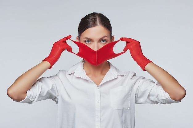Stijlvol jong meisje zet rood gezichtsmasker en handschoenen aan. Premium Foto