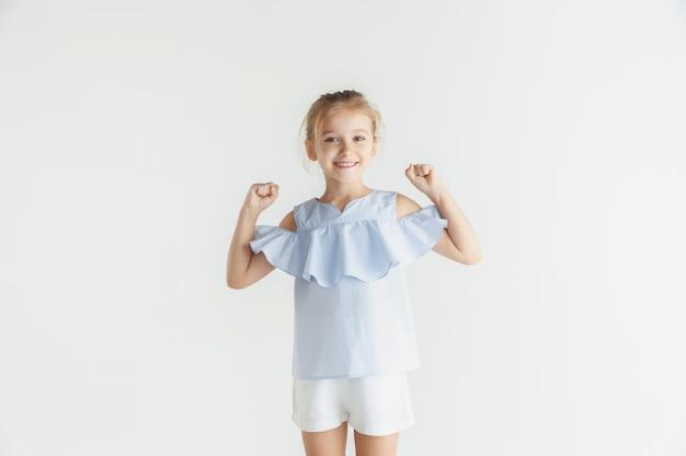 Stijlvol klein glimlachend meisje poseren in vrijetijdskleding geïsoleerd op witte studio achtergrond. kaukasisch blond vrouwelijk model. menselijke emoties, gezichtsuitdrukking, kindertijd. winnen, vieren, glimlachen. Gratis Foto