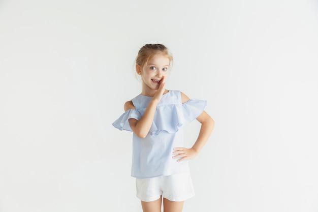 Stijlvol klein glimlachend meisje poseren in vrijetijdskleding Gratis Foto