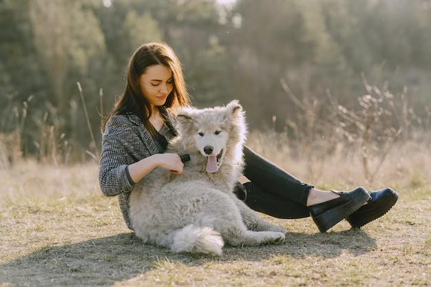 Stijlvol meisje in een zonnig veld met een hond Gratis Foto
