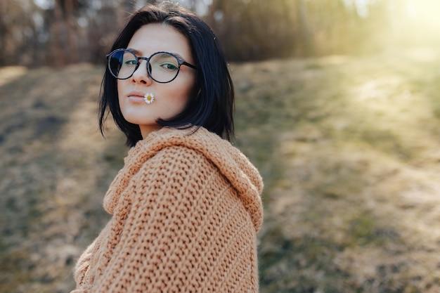 Stijlvol meisje op de achtergrond van het bos heeft een klein madeliefje in haar hand en lippen Gratis Foto