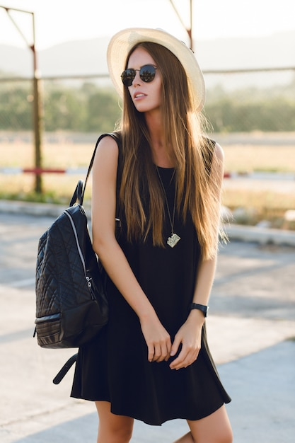 Stijlvol meisje permanent in de buurt van de weg, gekleed in korte zwarte jurk, strooien hoed, zwarte bril en zwarte rugzak. ze lacht in de warme stralen van de ondergaande zon Gratis Foto