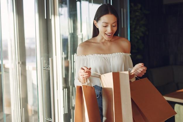Stijlvol meisje permanent in een café met boodschappentassen Gratis Foto