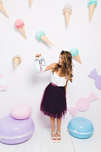 Stijlvol meisje zenuwachtig omdat de gasten te laat zijn voor haar verjaardagsfeestje. aantrekkelijke elegante jonge vrouw die in violette rok grote klok met verbaasde gezichtsuitdrukking bekijkt die zich in ingerichte kamer bevindt. Gratis Foto