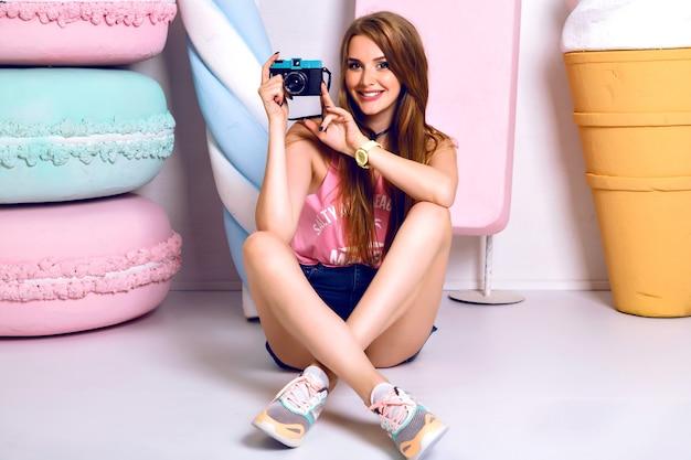 Stijlvol mode portret van vrolijke jonge vrouw zittend op de vloer, glimlachend en foto op camera nemen. blije emoties. positieve stemming. heldere kleurrijke levensstijl Gratis Foto