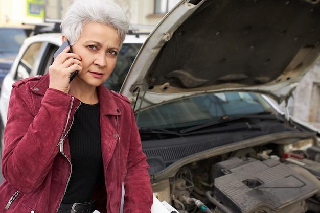 Stijlvolle aantrekkelijke grijze haren rijpe vrouwelijke bestuurder permanent in de buurt van haar gebroken witte auto met open kap en praten aan de telefoon Gratis Foto