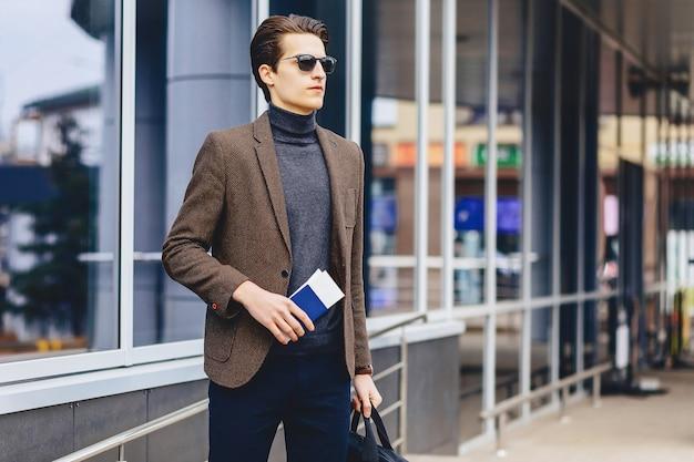 Stijlvolle aantrekkelijke kerel in jasje met paspoort en kaartjes Premium Foto