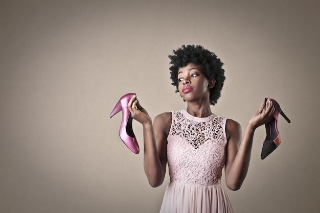 Stijlvolle afro-vrouw met een paar schoenen Premium Foto