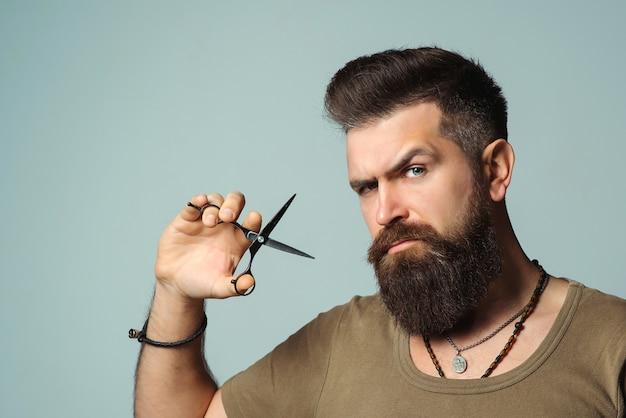 Stijlvolle bebaarde man. kapper met een schaar. klein bedrijf, kapper. knappe haarstylist. herenkapsel, baardverzorging. . Premium Foto