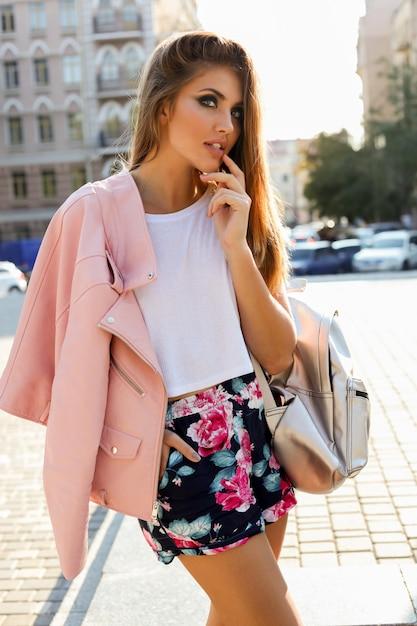 Stijlvolle blonde europese vrouw in roze lederen jas poseren buiten. Gratis Foto
