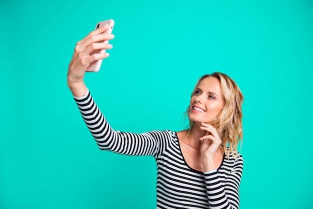Stijlvolle blonde vrouw in een gestreepte trui poseren tegen de blauwe muur Premium Foto