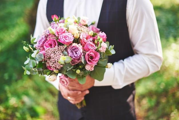 Stijlvolle bruidegom met een zacht roze bruiloft boeket. Gratis Foto