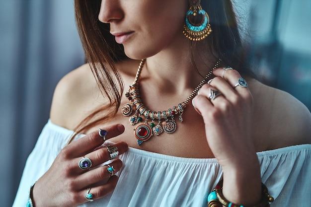 Stijlvolle brunette boho vrouw draagt witte blouse met grote oorbellen, ketting met steen en zilveren ringen. modieuze indiase hippie zigeuner bohemien outfit met imitatie sieraden details Premium Foto