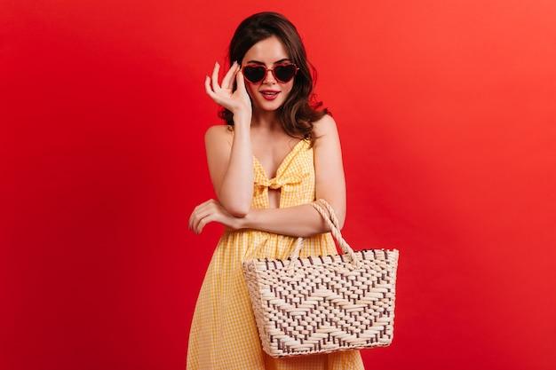 Stijlvolle brunette in gele zomerjurk zet een bril op in de vorm van harten. meisje met strandtas poseren op rode muur. Gratis Foto