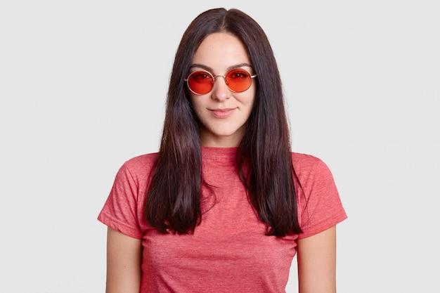 Stijlvolle brunette meisje draagt trendy rode ronde zonnebril, casual t-shirt, klaar om te lopen tijdens zonnige dag Gratis Foto