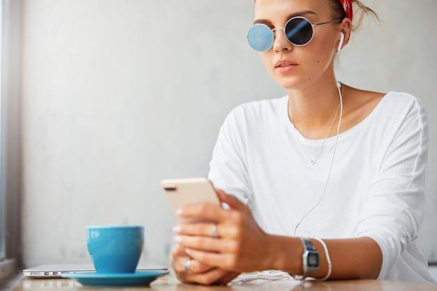 Stijlvolle charmante vrouw in tinten, maakt gebruik van moderne oortelefoons aangesloten op smartphone, kijkt naar interessante video of luistert naar audiotrack in sociale netwerken, maakt gebruik van gratis internetverbinding bij coffeeshop Gratis Foto