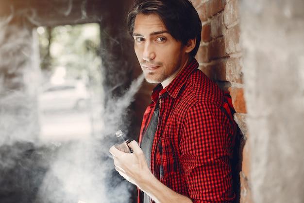 Stijlvolle en elegante man in een stad met damp Gratis Foto