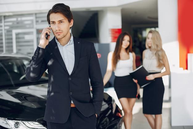 Stijlvolle en elegante mensen in een autosalon Gratis Foto