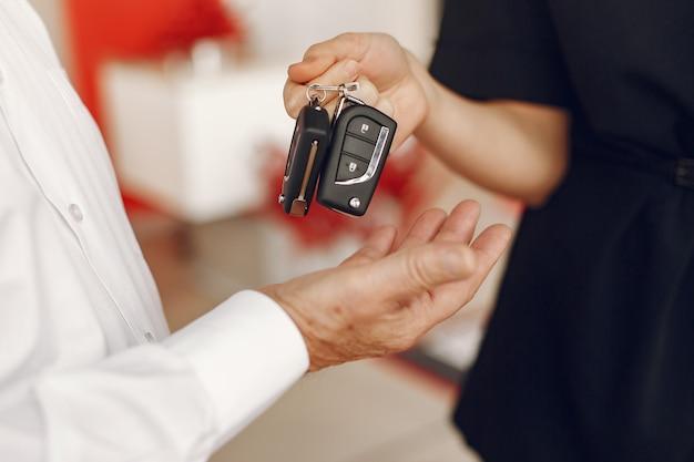Stijlvolle en elegante oude man in een auto salon Gratis Foto