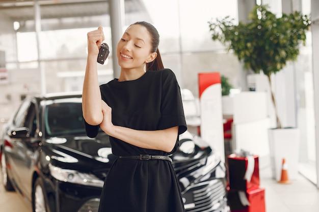Stijlvolle en elegante vrouw in een auto salon Gratis Foto