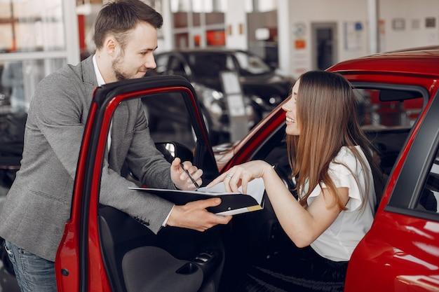 Stijlvolle en elegante vrouw in een autosalon Gratis Foto