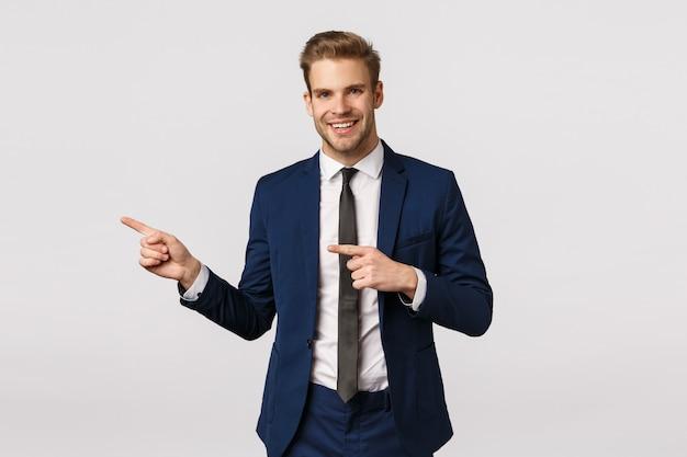 Stijlvolle en zelfverzekerde, knappe blonde bebaarde man in klassiek blauw pak, naar links wijzend, zakelijke partnerplaats tonen waar vergadering bespreken, uitnodigen binnen kantoor komen, staande witte achtergrond Premium Foto