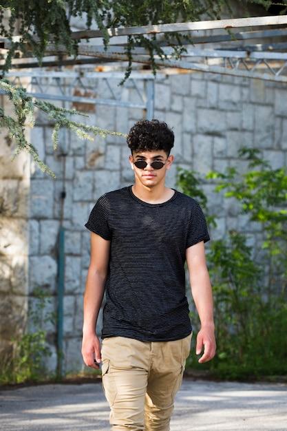 Stijlvolle etnische tiener man in zonnebril lopen op straat Gratis Foto