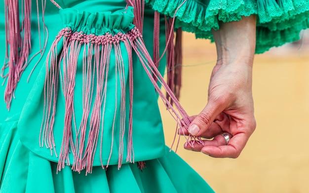 Stijlvolle flamencovrouw met groene vintage stoffen handtas met franjes Premium Foto