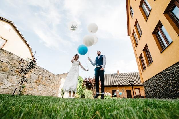 Stijlvolle gelukkige bruid en bruidegom houden ballonnen in handen en springen, poses Premium Foto