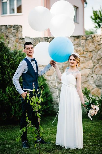 Stijlvolle gelukkige bruid met een boeket pioenrozen en bruidegom houden ballonnen in handen Premium Foto