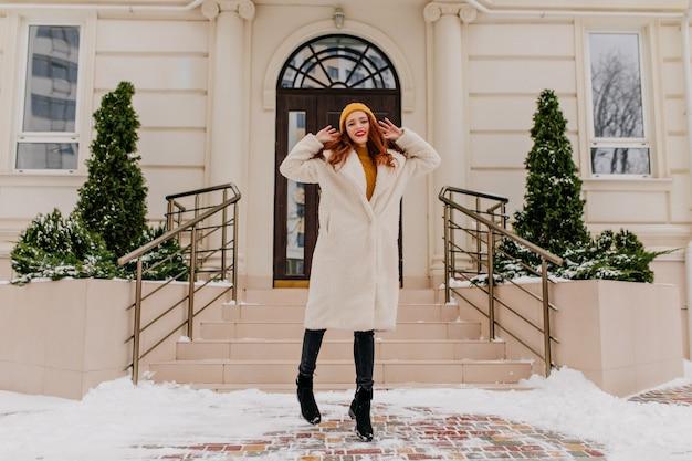 Stijlvolle gember vrouw in winterjas poseren voor mooi huis. buiten schot van elegant roodharig meisje. Gratis Foto