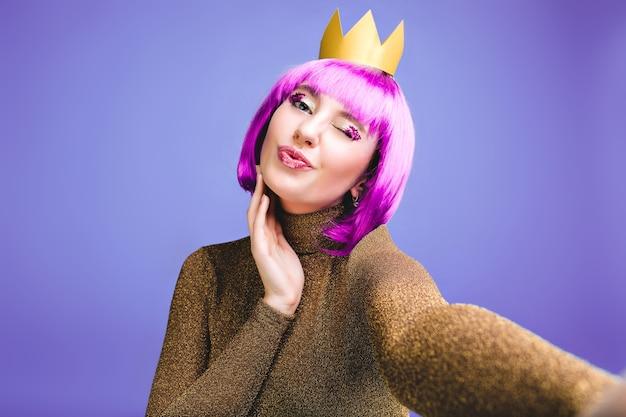 Stijlvolle heldere selfie portret modieuze jonge vrouw vieren feest. knip paars haar, aantrekkelijke make-up met tinsels, kus geven, vrolijke emoties, verjaardag, vakantie. Gratis Foto