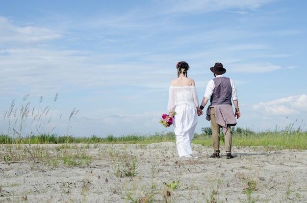 Stijlvolle hippie vrouw in witte etnische jurk hand in hand met man Premium Foto