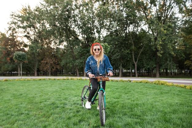 Stijlvolle hipster meisje rijdt op een fiets op groen gazon in het park Premium Foto