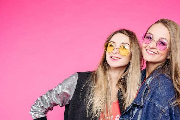 Stijlvolle hipster meisjes in kleurrijke zonnebril gelukkig lachend. Premium Foto