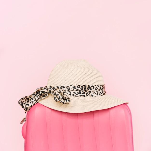 Stijlvolle hoed op plastic bagage reistas tegen roze achtergrond Gratis Foto