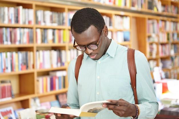 Stijlvolle jonge afro-amerikaanse man in overhemd en brillen op zoek via boek in de boekhandel staan. zwarte mannelijke toerist die lokale boekhandels verkent terwijl hij naar het buitenland reist Gratis Foto