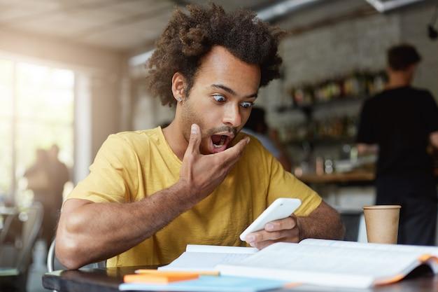 Stijlvolle jonge afro-amerikaanse mannelijke student met oorbel gekleed in geel t-shirt met verbaasde uitdrukking Gratis Foto