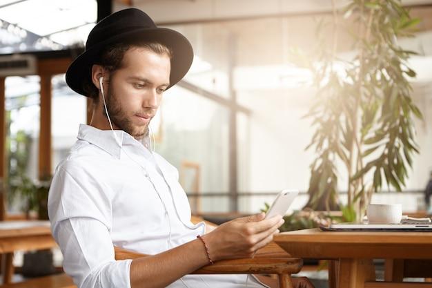 Stijlvolle jonge blanke man in zwarte hoed sms'en of post lezen via sociale netwerken met behulp van gratis wifi op zijn mobiele telefoon tijdens het ontbijt in gezellig café en luisteren naar muziek op oortelefoons Gratis Foto