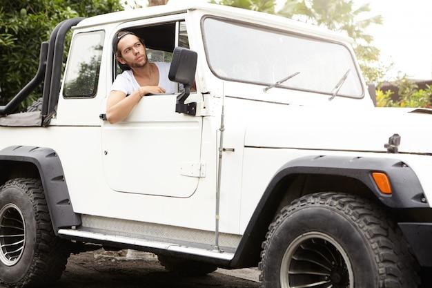Stijlvolle jonge blanke man kijkt uit open raam van zijn witte sport utility wagen. ongeschoren man met baseballpet achteruit rijdend in zijn jeep, genietend van een roadtrip Gratis Foto