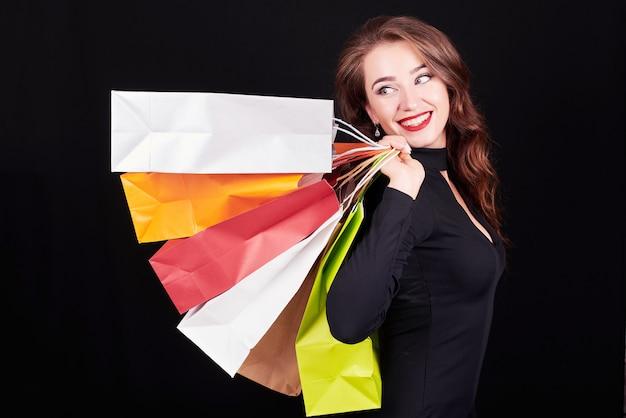 Stijlvolle jonge brunette vrouw met kleurrijke boodschappentassen Premium Foto