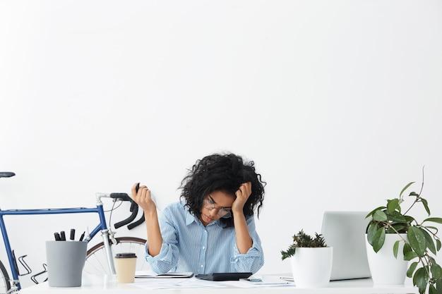 Stijlvolle jonge donkere vrouwelijke accountant in brillen en shirt werken vanuit huis Gratis Foto