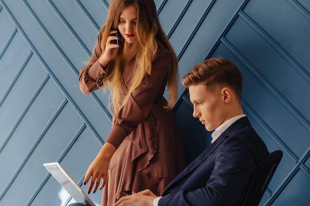 Stijlvolle jonge kerel met laptop en meisje met telefoon samen, jonge zakenman Premium Foto